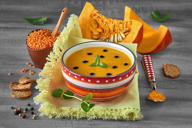Soupe épicée à la citrouille avec lentilles rouges et curcuma servie avec des feuilles de menthe et des gouttes de vinaigre balsamique