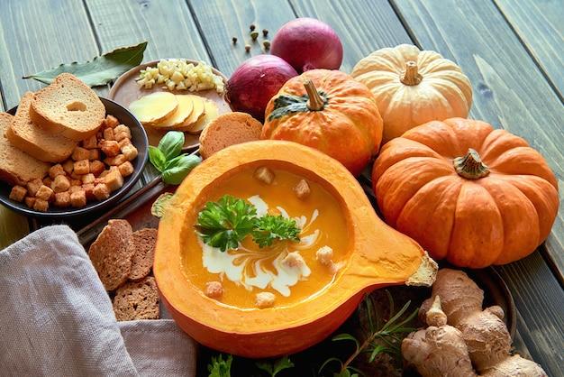 Soupe épicée à la citrouille servie dans une citrouille creuse avec ingrédients et espace de texte