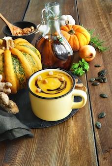 Soupe épicée à la citrouille servie dans une tasse avec de l'huile de citrouille et des croûtons