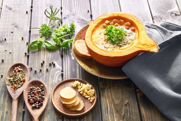 Soupe épicée à la crème de citrouille au gingembre et à l'ail dans une citrouille creuse