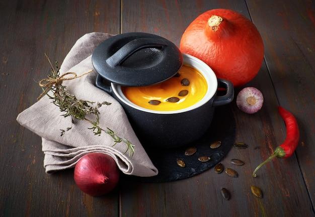 Soupe épicée à la crème de potiron avec oignons espagnols, ail et chili dans une poêle en céramique sur du bois foncé.