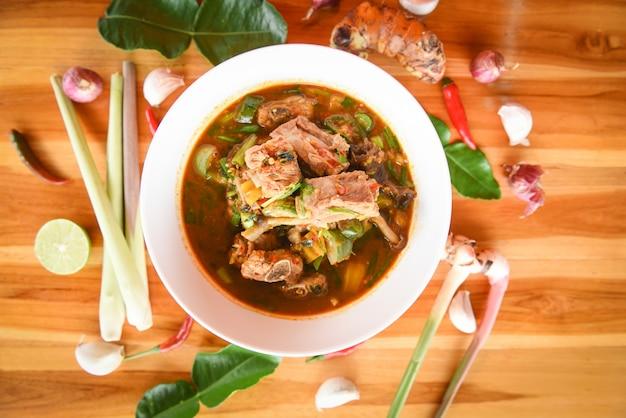 Soupe épicée de porc au curry / os de porc avec un bol à soupe aigre et piquant