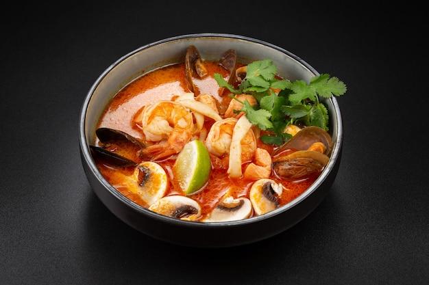 Soupe épicée thaïlandaise tom yam au lait de coco, crevettes tigrées, moules, calmars, truites et champignons. riz et citron vert