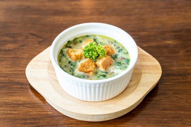 Soupe d'épinards avec du pain dans un bol blanc