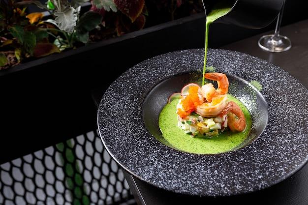 Soupe d'été okroshka aux crevettes tigrées et concombre frais dans une assiette noire
