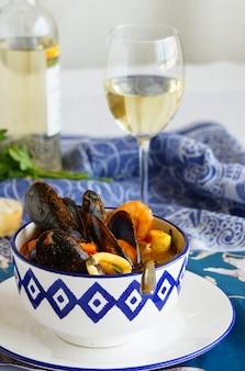 Soupe française bouillabaisse aux moules, palourdes, langoustines, calamars, morue, truite dans un bol blanc à motifs bleus