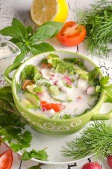 Soupe froide d'aliments crus d'été, okroshka dans un bol sur fond de bois blanc avec des ingrédients