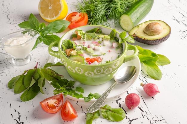 Soupe froide d'aliments crus d'été, okroshka dans un bol sur fond de bois blanc