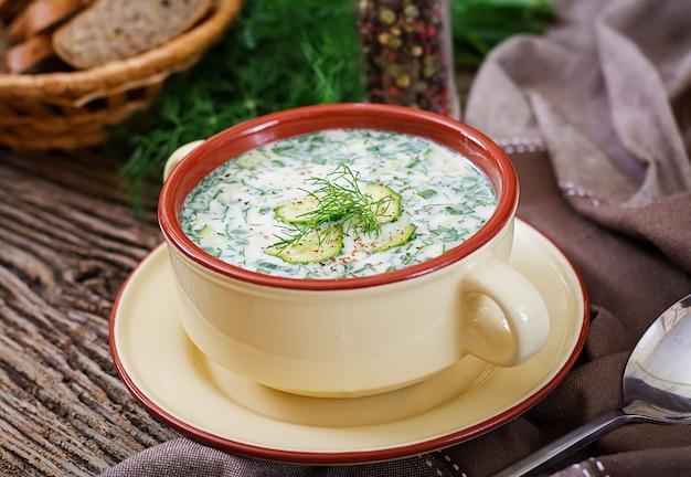 Soupe froide au yogourt d'été avec oeuf, concombre et aneth sur table en bois