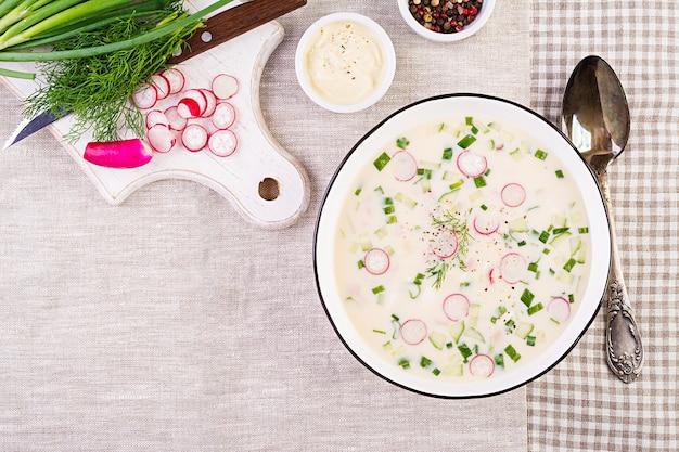 Soupe froide avec des concombres frais, des radis, des pommes de terre et des saucisses avec du yaourt dans un bol