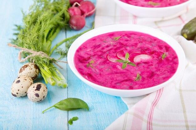 Soupe froide de légumes à la betterave et au yaourt naturel. bortsch froid - utile pour les journées chaudes. ingrédients soupe froide: œufs de caille, oignons verts, concombre, aneth, radis, basilic et yaourt naturel.