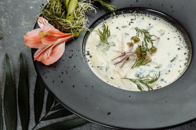 Soupe froide russe d'été traditionnelle avec kvas, okroshka avec jambon et légumes, nourriture.