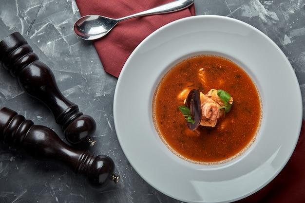 Soupe de fruits de mer frais dans une assiette blanche sur un espace sombre, vue de dessus