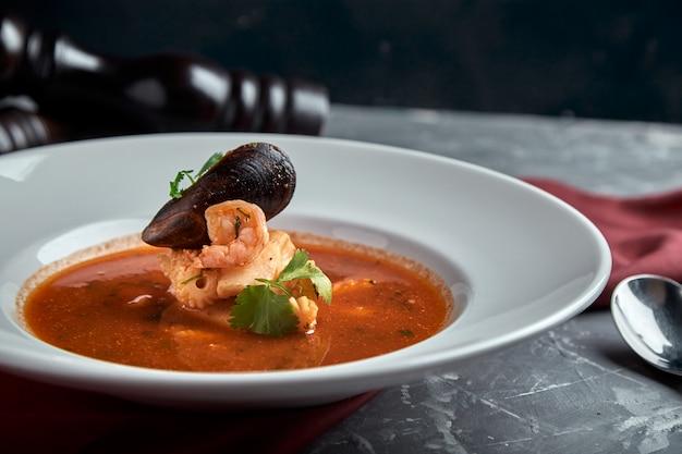 Soupe de fruits de mer frais dans une assiette blanche sur un espace sombre, vue latérale