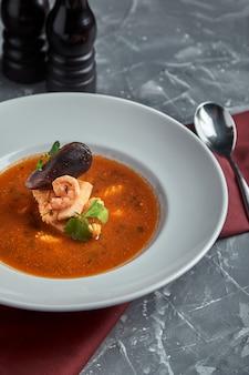 Soupe de fruits de mer frais dans une assiette blanche sur fond sombre, vue latérale