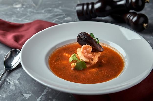 Soupe de fruits de mer frais dans une assiette blanche sur une surface sombre, vue de dessus