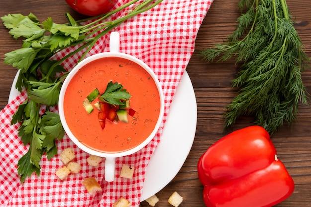 Soupe de gaspacho de tomates espagnoles à base de tomates fraîches avec diverses épices et herbes sur un fond en bois.