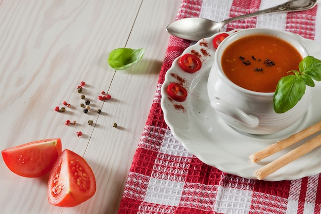 Soupe de gaspacho de tomates rouges fraîches sur la table avec les ingrédients. vue de dessus, gros plan, produits naturels frais