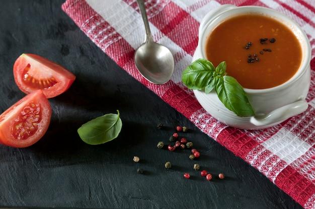 Soupe de gaspacho de tomates rouges fraîches sur une table en pierre noire avec les ingrédients.
