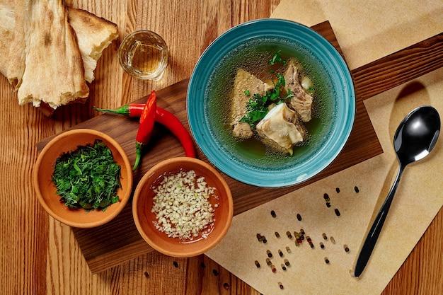 Soupe géorgienne au bœuf khashi avec sauce à l'ail verts shotis puri et chacha