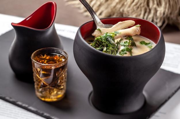 Soupe géorgienne chikhirtma avec volaille servie avec chacha
