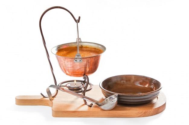 Soupe de goulash dans une casserole avec louche et assiette