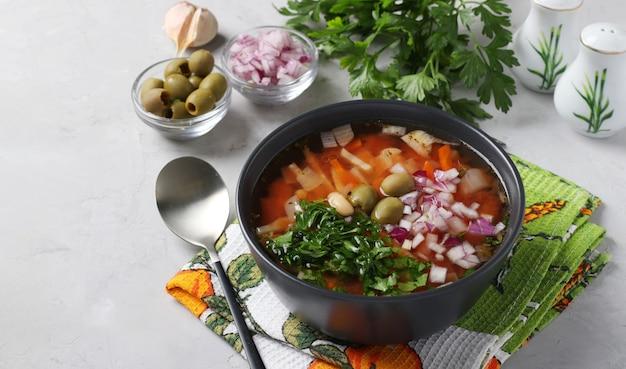 Soupe grecque aux tomates avec légumes, olives et haricots blancs dans un bol sombre sur fond gris