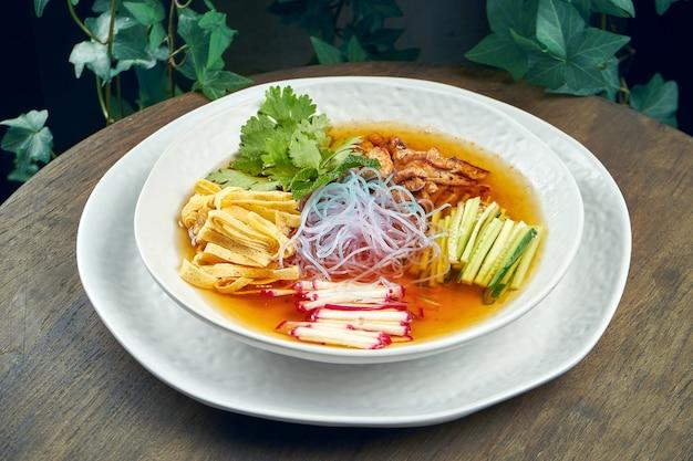 Soupe guksu coréenne froide avec nouilles de riz, coriandre et poulet dans un bol blanc sur une surface en bois.
