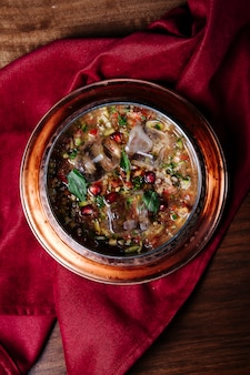 Soupe de haricots rouges aux herbes et épices dans une assiette en cuivre.