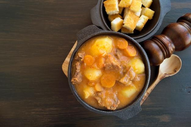 Soupe hongroise épaisse, le goulash. sur fond sombre.