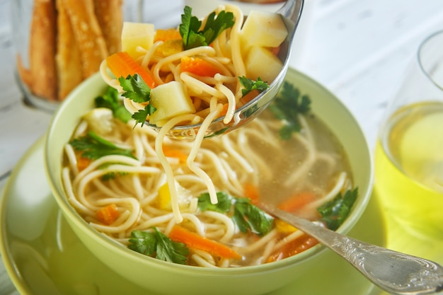Soupe italienne avec des spaghettis, des carottes, du citron, du persil et des morceaux de poulet dans une assiette verte, sur une table avec des serviettes, des cuillères de pain et une boisson dans un verre