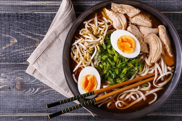 Soupe japonaise de ramen au poulet, œuf, ciboulette et germe sur fond de bois foncé.