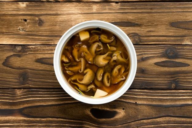 Soupe japonaise traditionnelle avec champignons shiitake, oignons et fromage tofu dans un bol en céramique blanche sur une table de cuisine en bois.