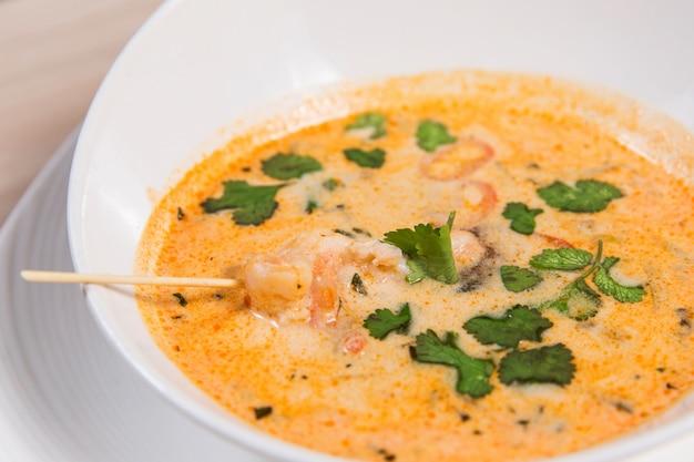 Soupe jaune avec crevettes dans un bol blanc sur une table en bois clair dans un restaurant