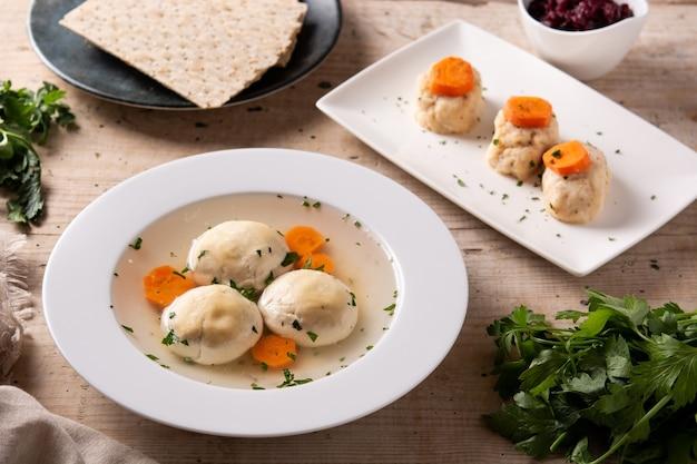 Soupe juive traditionnelle de boule de matsa, poisson de gefilte et pain de matsa sur la table en bois