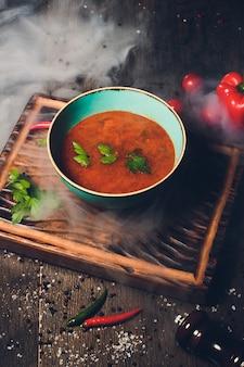 Soupe kharcho avec viande et riz sur table en bois.