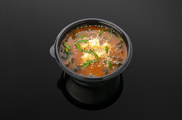 Soupe de kimchi au tofu, algues, sauce kimchi, handashi, oignon vert, œuf, sésame