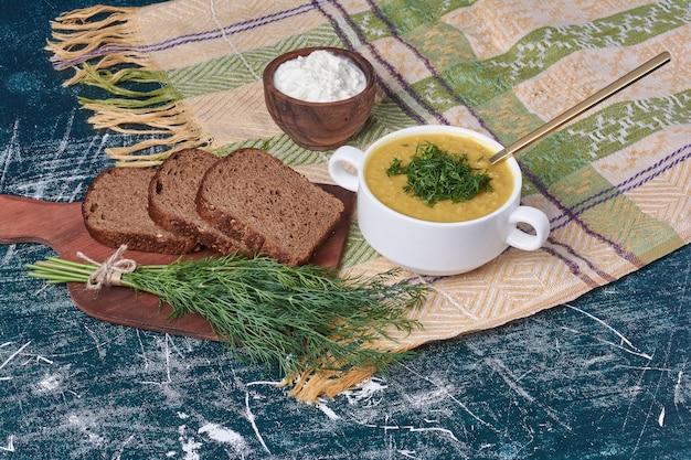 Soupe de légumes aux herbes et épices servie avec une tranche de pain grillé.