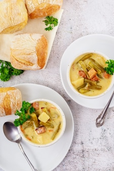 Soupe de légumes à base de haricots verts coupés, de carottes, de pommes de terre et de jambon.