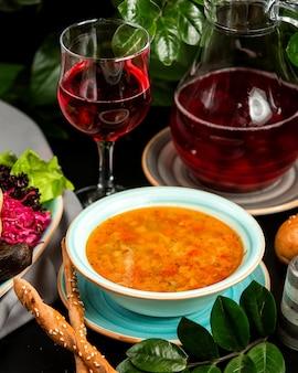 Soupe de légumes avec compote d'aubergines au chou mariné et gressins sur table