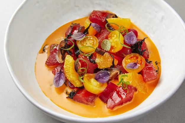 Soupe de légumes dans un bol blanc, avec tomates cerises, poivrons, betteraves et herbes