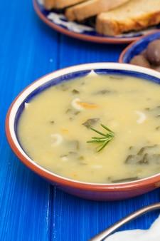 Soupe de légumes dans un bol et des olives avec du pain de maïs