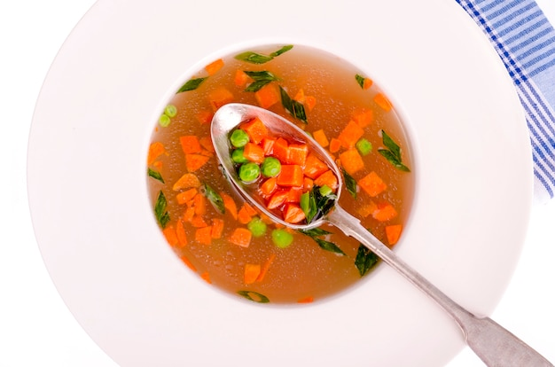 Soupe de légumes diététiques avec carottes, pois et oignons verts.