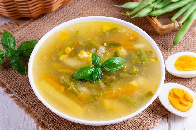 Soupe de légumes frais faite de haricots verts, pois, carottes, pommes de terre, oeuf dans un bol au basilic