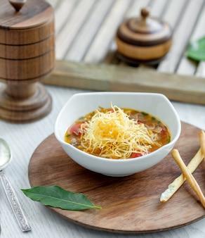 Soupe de légumes garnie de lacets de pommes de terre et de baguettes de pain