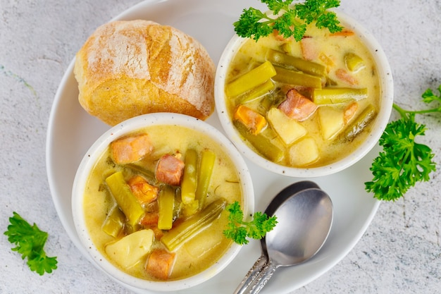 Soupe de légumes maison avec pois verts coupés, pomme de terre et viande. vue de dessus.