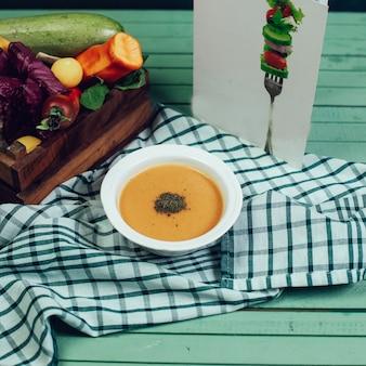 Soupe de lentilles rouges aux épices sur une nappe à carreaux.
