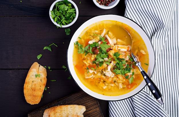 Soupe de lentilles rouges avec viande de poulet et légumes gros plan sur la table. la nourriture saine. vue de dessus
