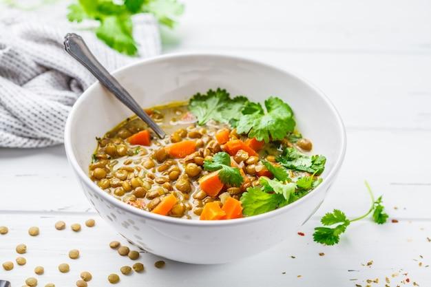 Soupe de lentilles végétalienne faite maison avec des légumes et de la coriandre, fond en bois blanc.