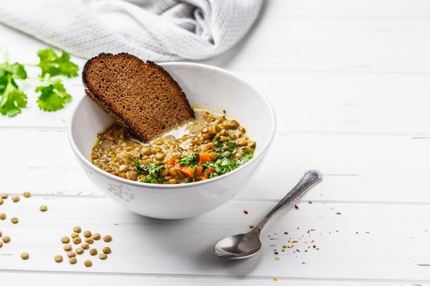 Soupe de lentilles végétalienne faite maison avec légumes, pain et coriandre, fond en bois blanc.